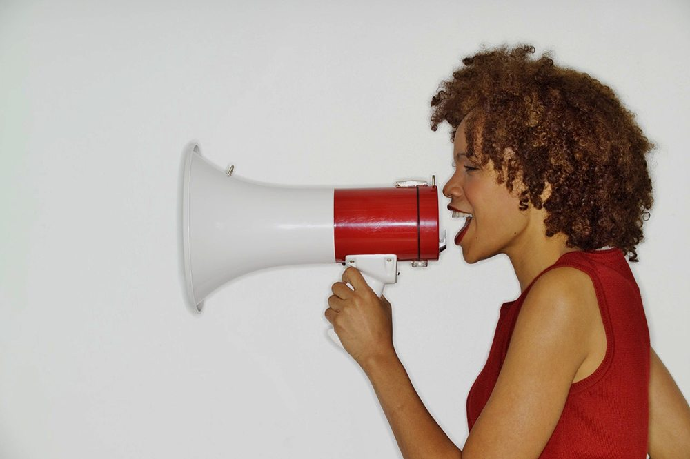Woman Using Megaphone --- Image by © Royalty-Free/Corbis